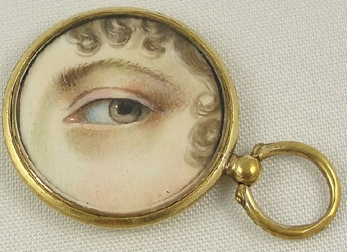 Lover's eye handpainted on ivory of a beautiful woman with a hazel eye, surrounded by brown curls. Mounted in gold shell pendant