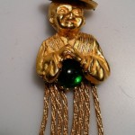 Possibly Selro brooch made in the shape of an Asian man embracing a green crystal ball