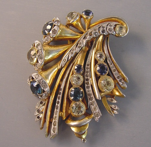 Ralph DeRosa fur clip with deep blue, pale yellow and clear unfoiled and foiled rhinestones set in gilt silver metal, signed 'R DeRosa' on the back, circa 1940
