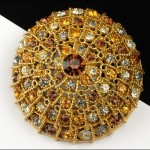 Golden tone round brooch with rhinestones