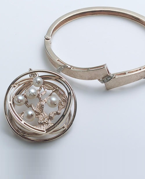 A diamond and 14k gold hinged bangle bracelet, a cultured pearl and gold 'Tree of Life' charm