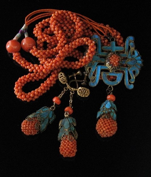 Coral beads and encrusted with blue kingfisher feathers decorations