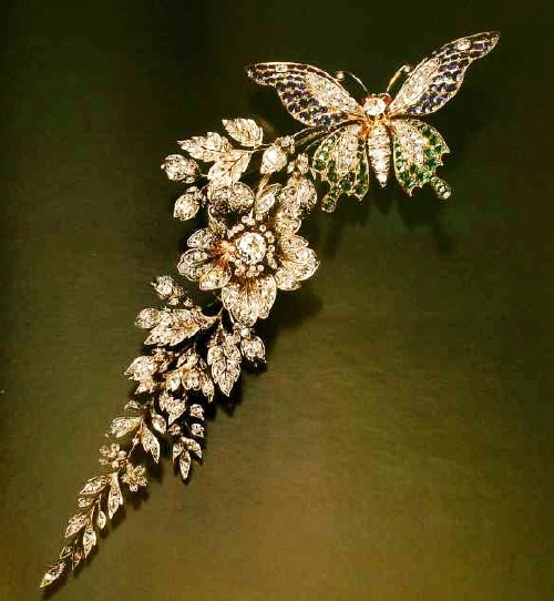 Exquisite brooch with emeralds, sapphires, rubies and diamonds in the shape of a butterfly sitting on a branch of wild rose. 1880. France