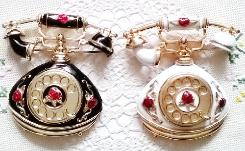 2 massive brooches in the shape of antique phones from AJC. Made of enamel, in white and black, decorated with roses