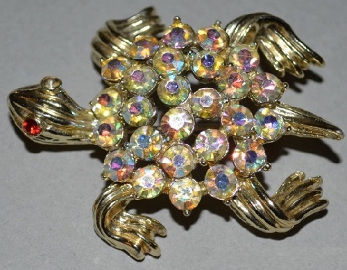 Elegant brooch costume jewellery alloy of golden color with a scattering of sparkling crystals, by the company BSK