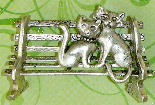 Vintage Brooch by AJC Cats on a bench