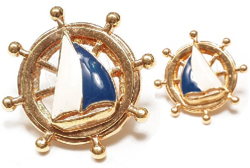 Avon Stud earrings in the form of a ship's wheel, with the image of sails, labeled, end of 1980s. Costume jewellery alloy, enamel
