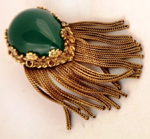 Brooch made of antique gold color metal. In the center a large brooch teardrop-shaped green cabochon. Cabochon framed with floral motifs. Below refined suspension of the chains