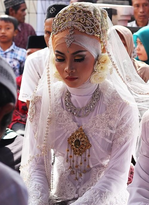 Indonesian bride today - in a white embroidered dress, decorated with lots of jewellery - tiara, necklace, earrings