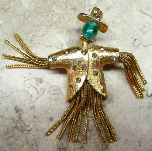 Pauline vintage brooch. Gold tone metal scarecrow, green art glass cabochon, rhinestones