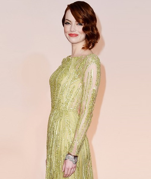 US actress Emma Stone in paired cuff bracelet from Tiffany & Co of Blue Book Collection Gold, diamonds. at the Oscars 2015