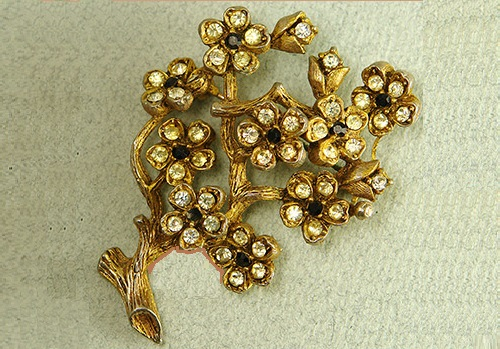 Vintage brooch Blossoming branch. The jewellery alloy coated antique gold, inserts - transparent crystal and black rock crystals. Marked - © HAR, 1960. United States