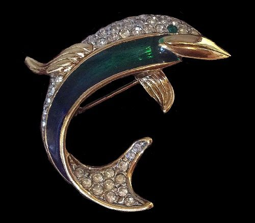 Elegant vintage brooch in the form of a dolphin. The base made of a gold-tone jewelery alloy. Decorated with a Swarovski crystals, enamel and varnish. Marked A & S. 1980s
