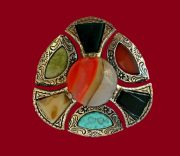 A large and heavy brooch made of metal of bronze color with multi-colored cabochons imitating semi-precious and ornamental stones - jasper, turquoise, agate. 1950