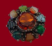 Flower brooch. Made of metal for antique silver with multi-colored cabochons imitating semi-precious stones - jasper, turquoise, malachite, agate. The center adorned with a stone of dark brown color