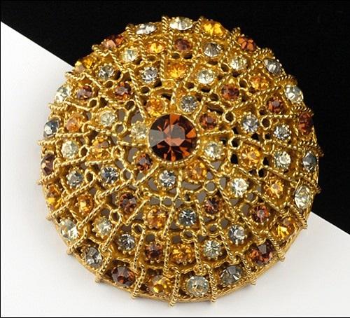 Golden tone round brooch with rhinestones