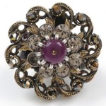 Brooch: metal, gilding, engraving, filigree, glass cabochons. 1940s