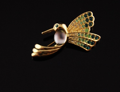 Hummingbird brooch with a mirror shining cabochon and Swarovski crystals from clear to emerald green adorning the wings