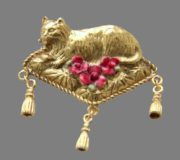 Cat resting on a fancy pillow with tassels. Gold tone brooch decorated with three red enamel flowers