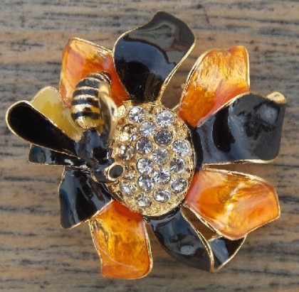 A very realistic enamel flower, with a bee sitting on it