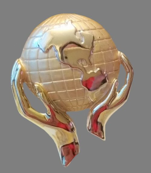 Hands holding Planet Earth gold tone brooch. 4.3 cm