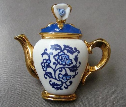 Original design from the company Avon, a collection of 1997. Brooch in the form of a porcelain teapot painted white and blue