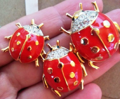 Ladybug brooch and clipss. Gold tone jewellery alloy, red glossy enamel; crystals