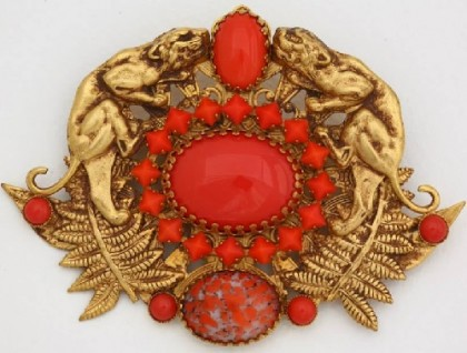 Wildcats' brooch from the first collections of the 1980s, the most valuable to collectors. Brass alloy, gold plated, inserts – old Czech glass of coral color. Excellent details show every muscle on the body of panthers, every vein on the leaves in the bottom