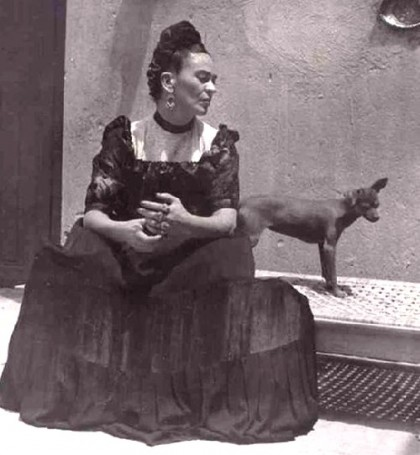 Black and white photo of Frida Kahlo with a dog