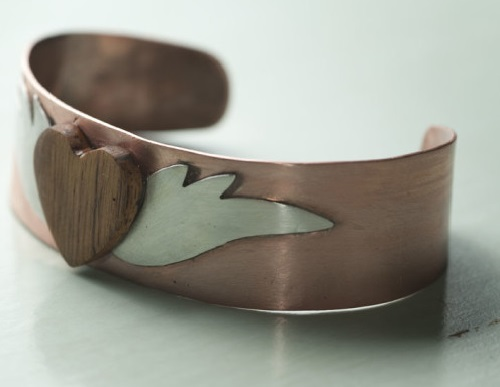The winged heart bangle of copper, the wings are silver and the heart is carved out of wood