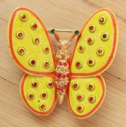 Butterfly brooch with green wings with dots. Bright multi-colored crystals and enamel