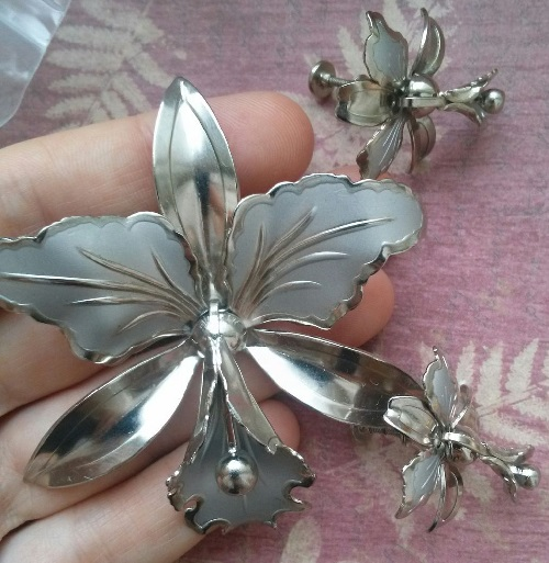 Set of brooch and screw earrings. Made of an alloy of silver. Some petals decorated with matte silver enamel