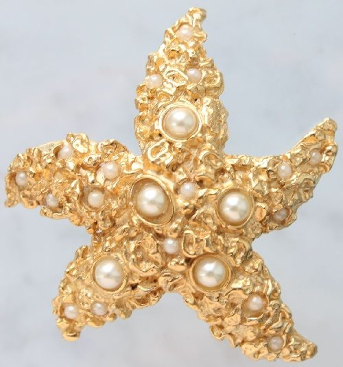 Starfish original brooch with cabochons imitating pearls. Jewelry alloy of gold color and elegant shape