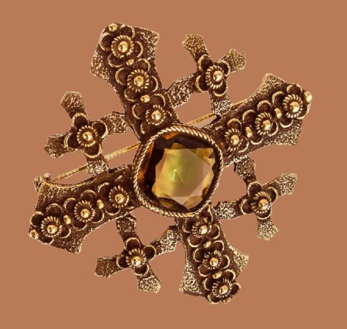 The Maltese cross brooch-pendant, a jewelry alloy of antique color, decorated with a large green-yellow crystal. Marked by Accessocraft N.Y.C., 1950s