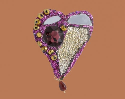 The purple heart-shaped brooch, from a series of created in India in 2015. The hues of purple with the gold beads and the textured glass make this piece a wearable art