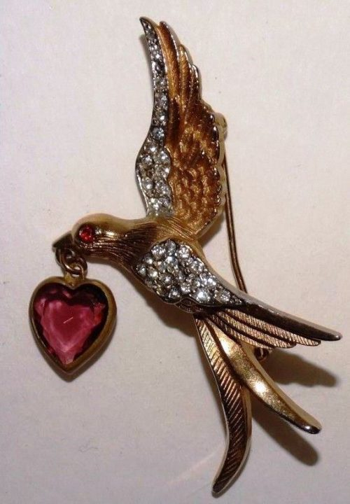 A bird with a heart brooch