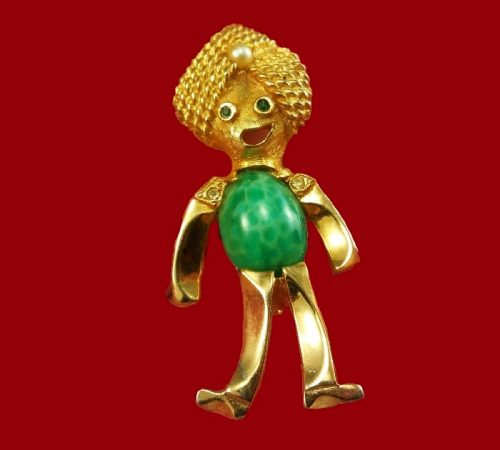 A funny smiling figure in a turban, brooch from Kramer. Green Beijing glass, a turban decorated with a pearl, green crystals