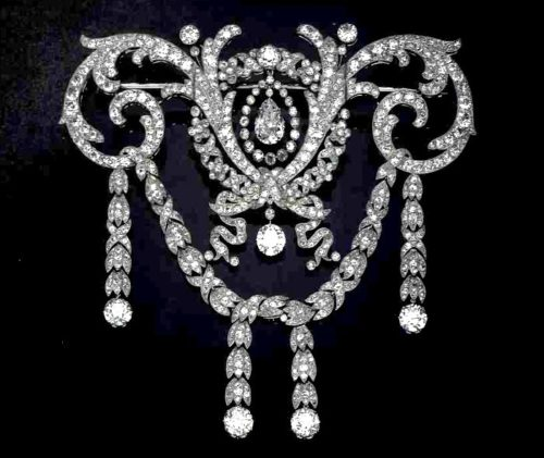 A 1909 diamond and platinum corsage ornament by Cartier showcases the Versailles motifs - flowers, ribbons, and scrolls. Large circular-cut diamonds accent the festoons. At the center is a pear-shaped diamond in a diamond-collet frame, a signature Cartier motif.