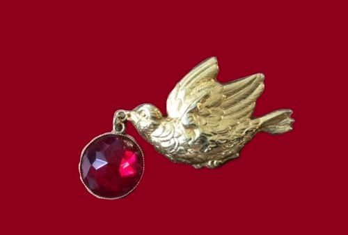 A bird carrying a ruby charm. pin brooch made of metal and faux ruby