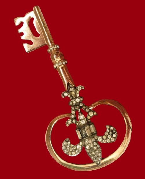 Antique brooch in the form of a large key with a royal lily. Silver gilt with inlaid rhinestones vintage patterns