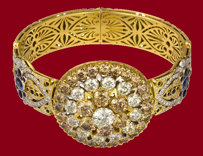 A massive bracelet - a skillful interlacing of ornaments and smooth lines of diamonds. The solar symbol in the center organically closes the composition, crowning the gold base with large diamonds