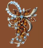 Bow and flower brooch. Faux amber, blue rhinestone and gold tone metal