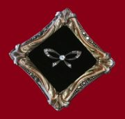 Bow in a frame brooch, jewelry alloy, colored enamels, silvering, silver, crystals. Size 6.5 cm