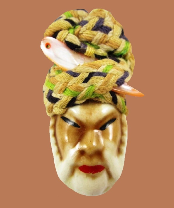 Ceramic brooch from the series 'Victim of fashion', 1940s. Ceramic face, fabric hat with mother of pearl accent. Wood backing with a metal pin assembly