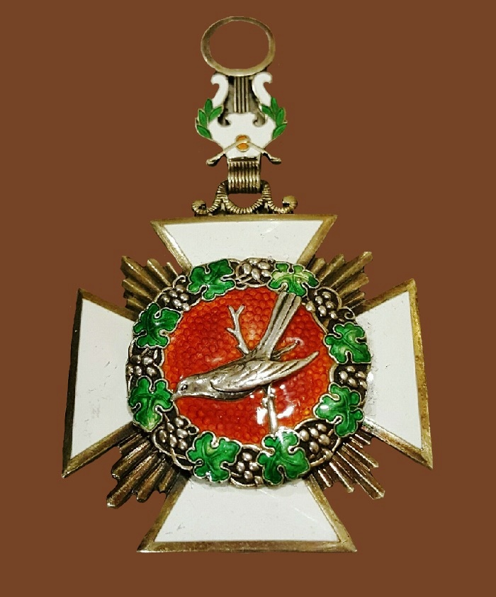 Cross medal depicting bird sitting on the branch, harp on the top