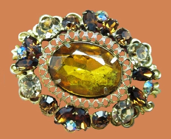 Luxurious vintage brooch. Brass, lace ornament, art glass inlays of apple juice and honey color