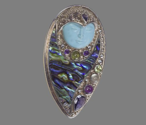 Mysterious vintage jewelry brooch-pendant. Decorated with fine granulation of silver, multi-colored stones and mother of pearl with a magnificent game of shades-heliotis