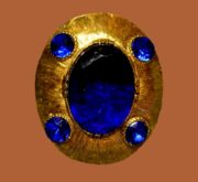 Oval brooch. Gold tone jewellery alloy, gilding, sapphire crystals