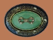Oval framed brooch with a bow. Jewelry alloy, enamel, crystals