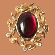 Oval gold tone brooch with a large oval red glass